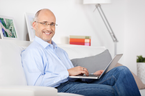 Smiling man sitting on the couch and browsing the internet - stock photo